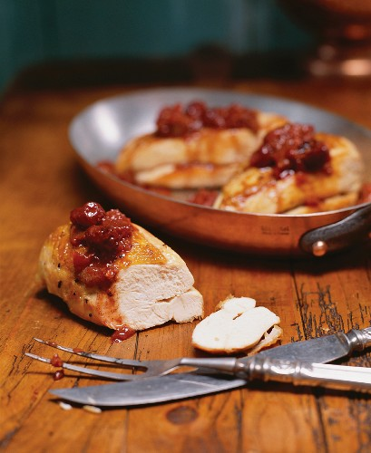 Chicken Breasts Topped with a Cherry Rhubarb Chutney; One Cut on Wooden Table; Some in Pan; Carving Set