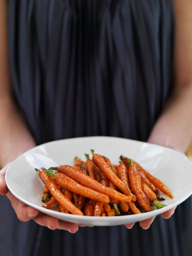 A woman serving glazed carrots with balsamic vinegar