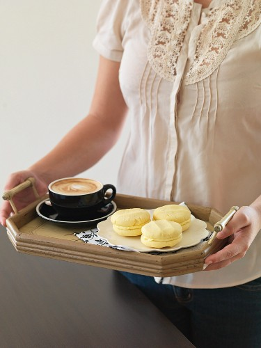 A woman holding a tray of coffee and Melting Moments