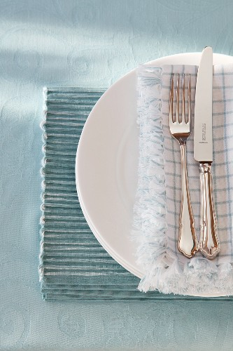 A place setting with silver cutlery on a place mat