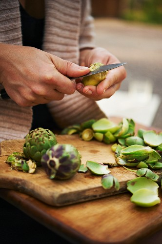 Woman Using a Knife to Peel Baby Artichokes Over a Wooden Cutting Board