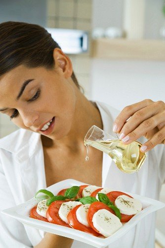 Woman pouring olive oil on antipasto