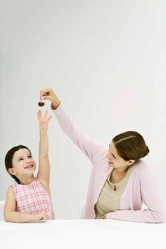 Mother holding up cherries, daughter reaching, both smiling