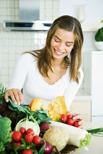 Young woman in kitchen, looking down at assorted fresh vegetables, smiling
