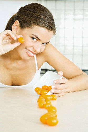 Young woman spilling dish of cherry tomatoes, smiling at camera
