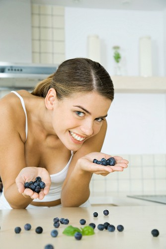 Woman in kitchen, holding handfuls of blueberries, smiling at camera