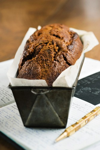 A loaf cake in a baking tin on a book