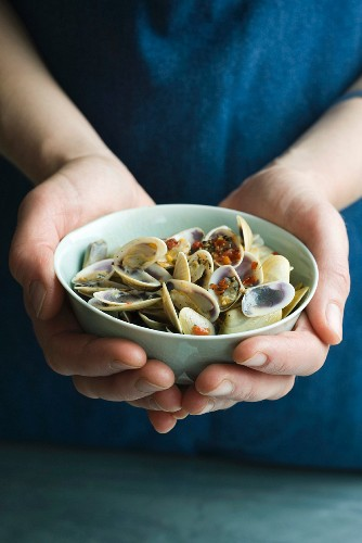 A person holding a bowl of Venus clams with limes and chilli paste
