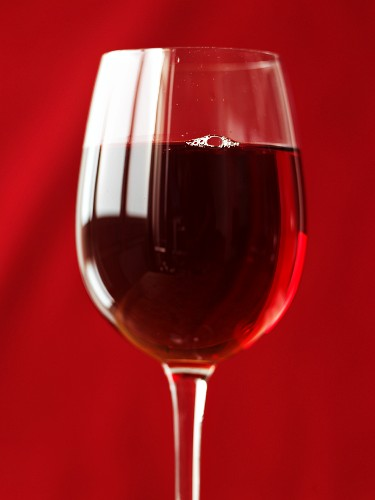 A glass of red wine in front of a red background