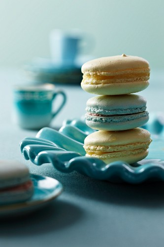 Three Blue and Yellow Macaroons; Stacked on a Blue Plate