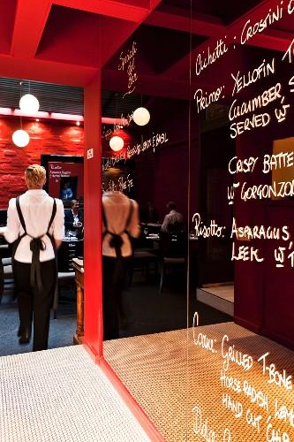 A specials board written on a mirror in a restaurant