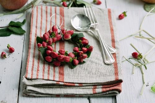 Small wreath of hypericum berries on linen napkin