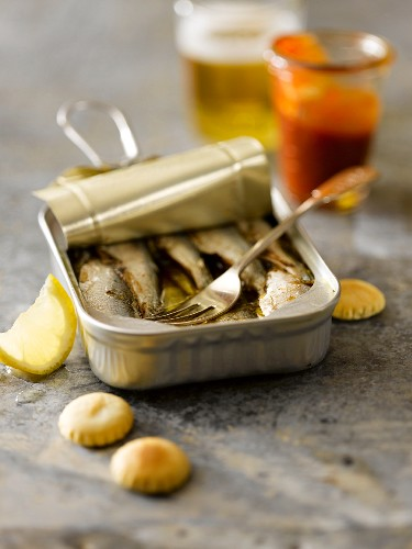 Open Can of Sardines with a Cocktail Fork; Oyster Crackers and Cocktail Sauce; Beer