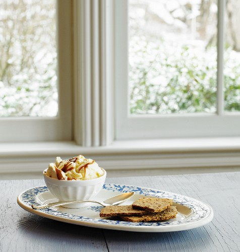 Vanilla ice cream with caramel drizzle and sesame crackers on a windowsill