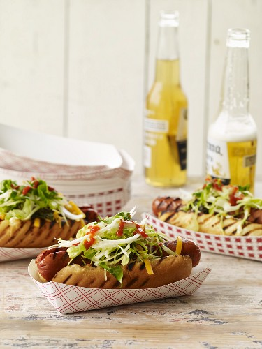 Grilled Hotdogs in Cardboard Dishes with Bottles of Beer