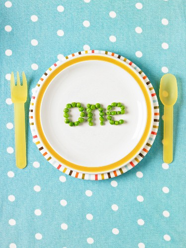 """The word """"one"""" spelled out with peas on a plate"""
