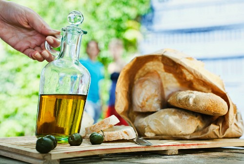 A jug of olive oil, ciabatta bread and olives on a wooden board
