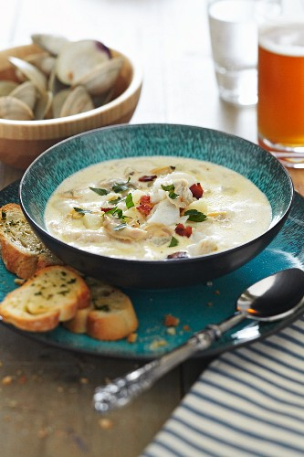Bowl of New England Clam Chowder with Garlic Bread and Beer