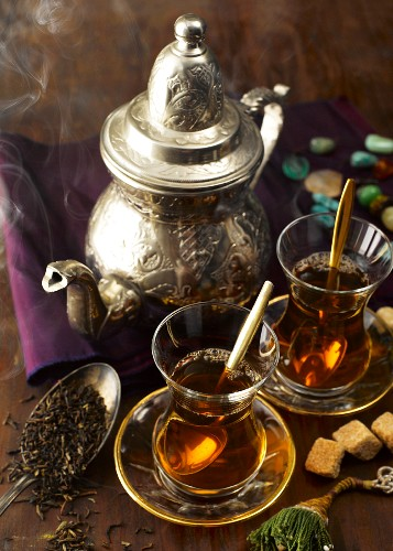 Oriental black tea in glasses and a silver teapot