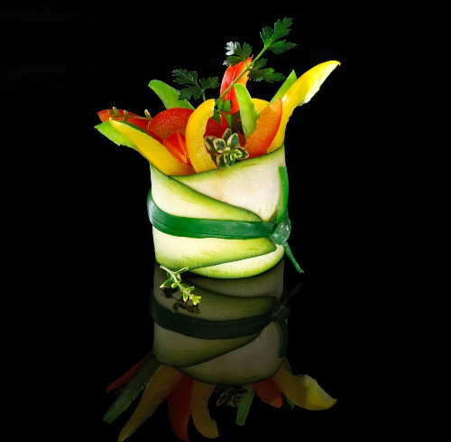 Colourful pepper sticks and parsley wrapped in a courgette slice