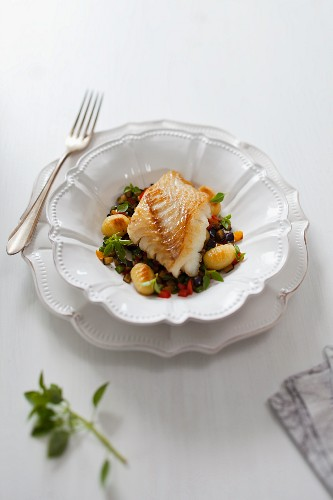 Cod fillet on a bed of vegetables and gnocchi