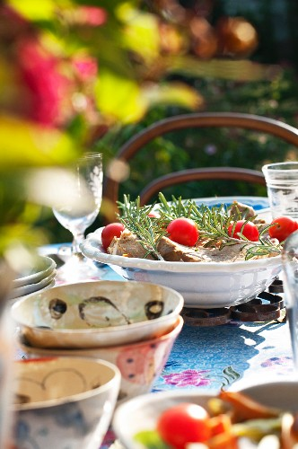 Pork chops with rosemary and cherry tomatoes on a summery table