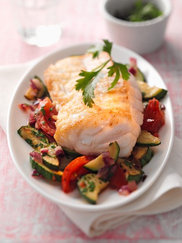 Fish fillet on a bed of courgette and tomatoes