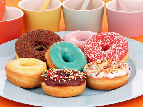 Colourfully glazed doughnuts on a plate