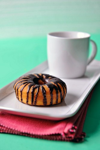 A doughnut with chocolate glaze and a cup