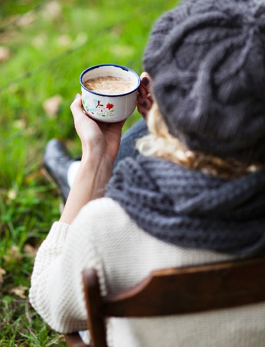 A woman with a cup of coffee on a chair outdoors