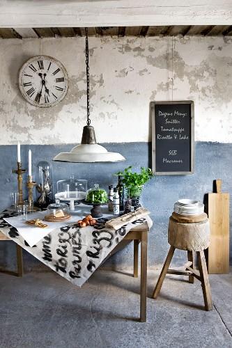 Vintage-Tisch mit Lebensmitteln und Küchenutensilien unter Glasglocken; dahinter eine rustikale Wand in Weiss und Blau