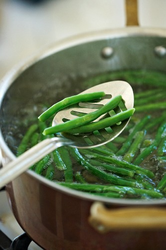 Slotted Spoon with Green Beans Boiling in a Copper Pot