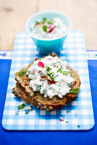 A slice of wholemeal bread topped with cottage cheese on a breakfast tray