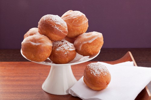 Several doughnuts coated with sugar glaze or icing sugar, on a cake stand against a purple background