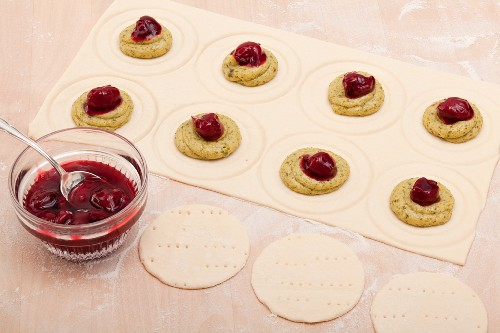 Small galettes being filled with pistachio cream, with a bowl of preserved cherries to one side