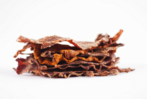 Slices of Beef Jerky Stacked on a White Background