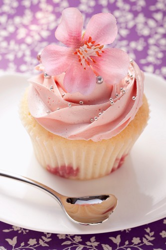 A cupcake garnished with a pink flower