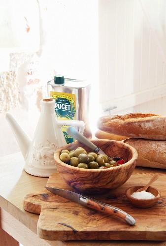 Oliven, Olivenöl, Brot, Salz & Taschenmesser auf Holzbrett in Küche des Chateau Maignaut (Pyrenäen, Frankreich)
