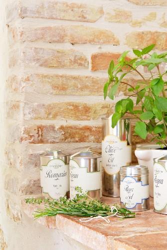 Mediterrane Kräuter & Olivenöl in Metalldosen auf gemauerter Ablage im Chateau Maignaut (Pyrenäen, Frankreich)
