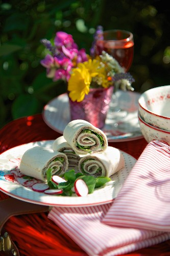 Wraps with roast beef and radishes, on a picnic basket