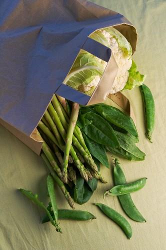 Asparagus, pea pods, sorrel and cauliflower in a shopping bag