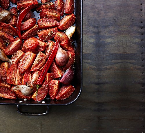 Slow roasted tomatoes with onions and garlic in a roasting dish