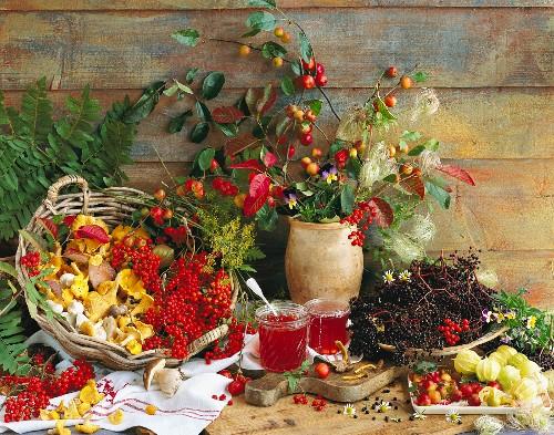 An autumnal arrangement of chanterelle mushrooms, rowan berries, elderberries, ornamental apples, Cape gooseberries and rowan berry and apple jelly