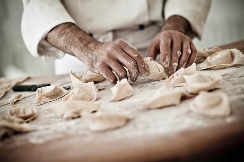 A chef rolling fresh tortellini in flour
