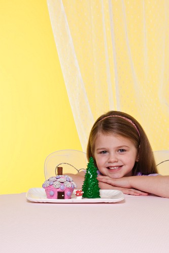 A Little Girl Wearing Fairy Wings Next to a Fairy House Cake