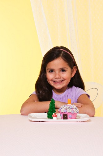 A Little Girl with Dark Hair Wearing Fairy Wings Next to a Fairy House Cake