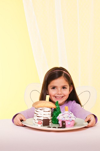A Little Girl Wearing Fairy Wings Smiling by a Plate of Fairy House Cakes