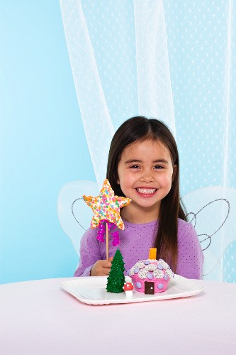 A Little Girl Holding a Star Shaped Cake Pop Next to a Plate with a Fairy Cake and Tree