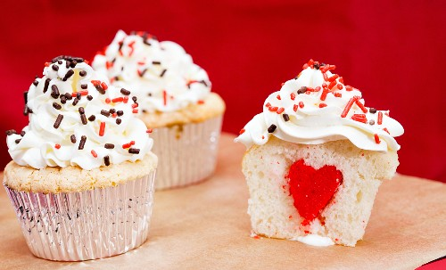 Cupcakes mit Sahnecreme und rotem Herz in der Mitte