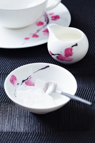 A teacup, a small milk jug and a sugar bowl of white rock sugar, all with a flower design